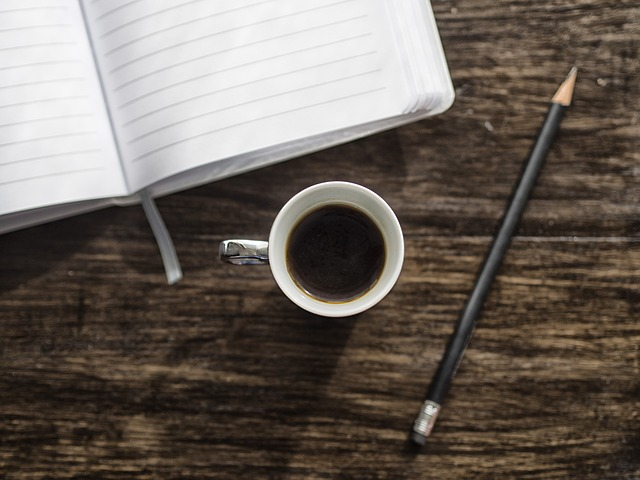 Coffee cup, pencil, notepad